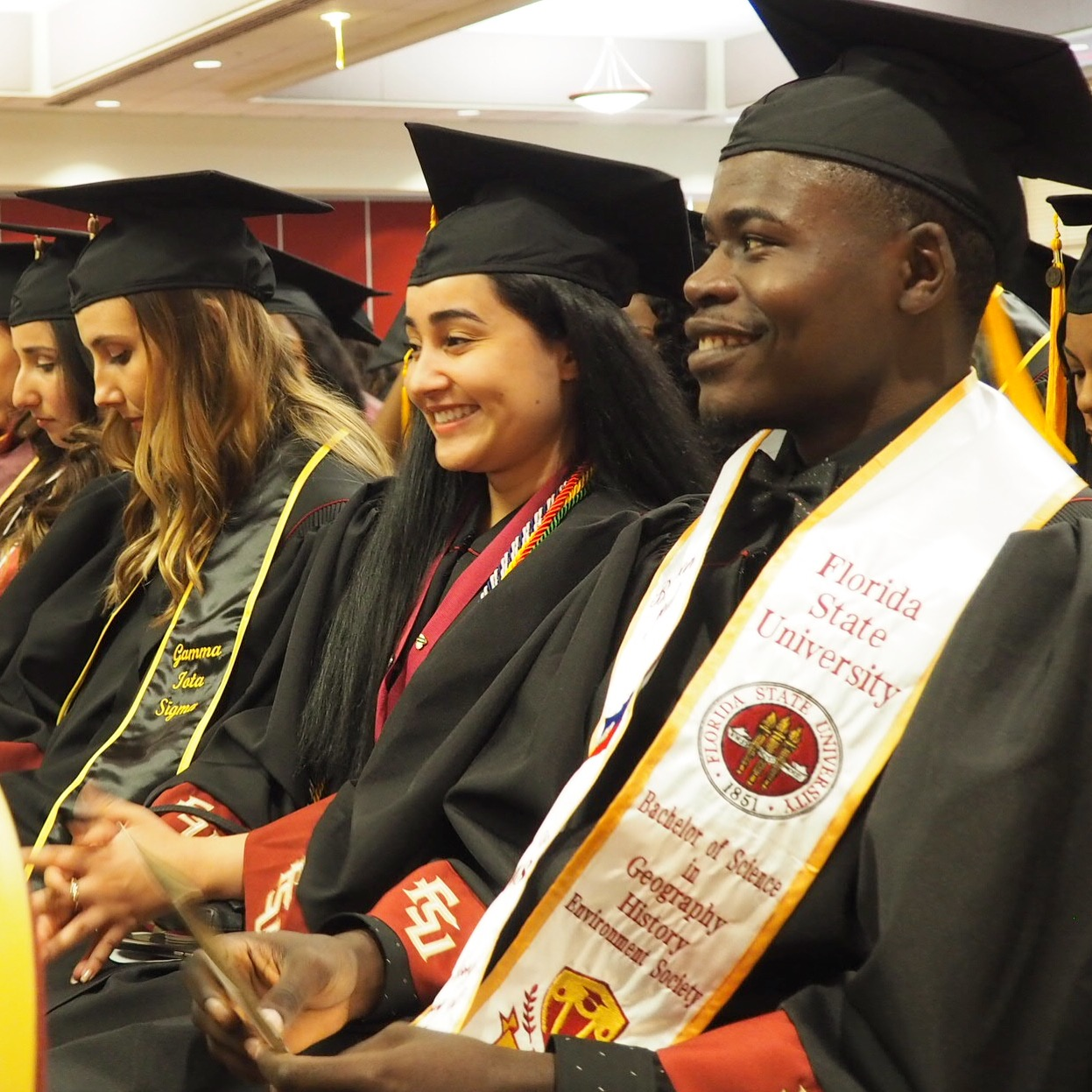 Students in caps and gowns smile at the start of the cultural gradaution ceremony.