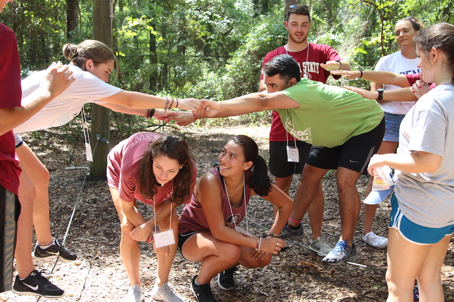 IMAGE: Students try to balance on a cable as they complete a challenge course during the first day of Service Leadership Seminar.