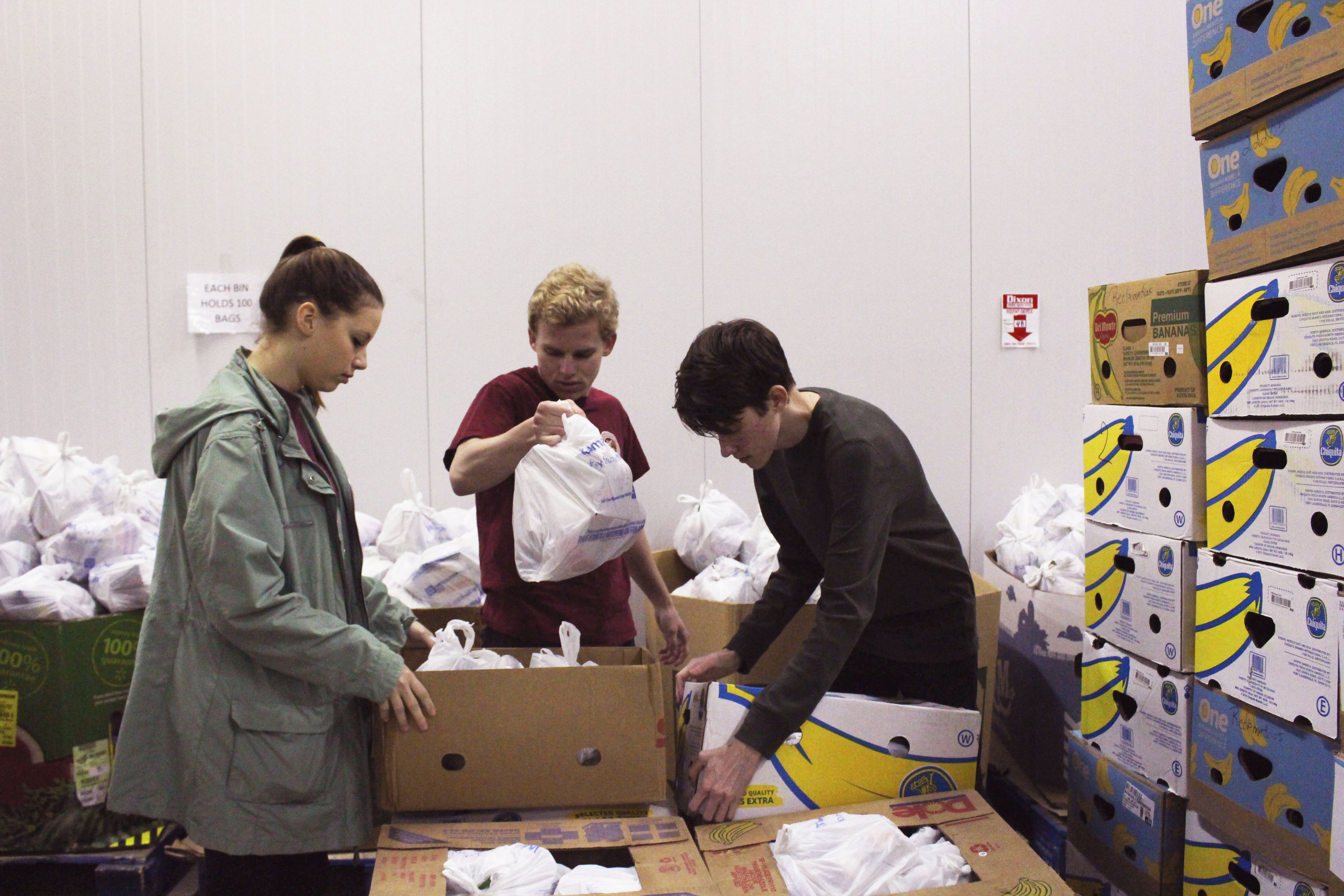 Three students sort food at Second Harvest of the Big Bend during a pre-remote community engagement program.