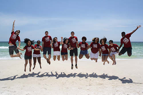 Students wearing Center for Leadership and Social Change shirts holding hands and jumping together above the sand of a beach