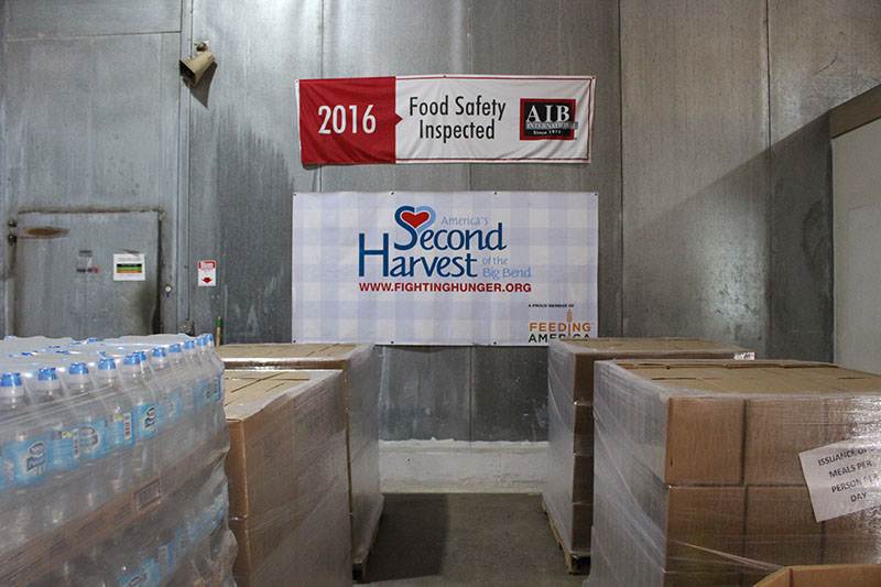 Second Harvest sign seen hung above stacks of boxes.