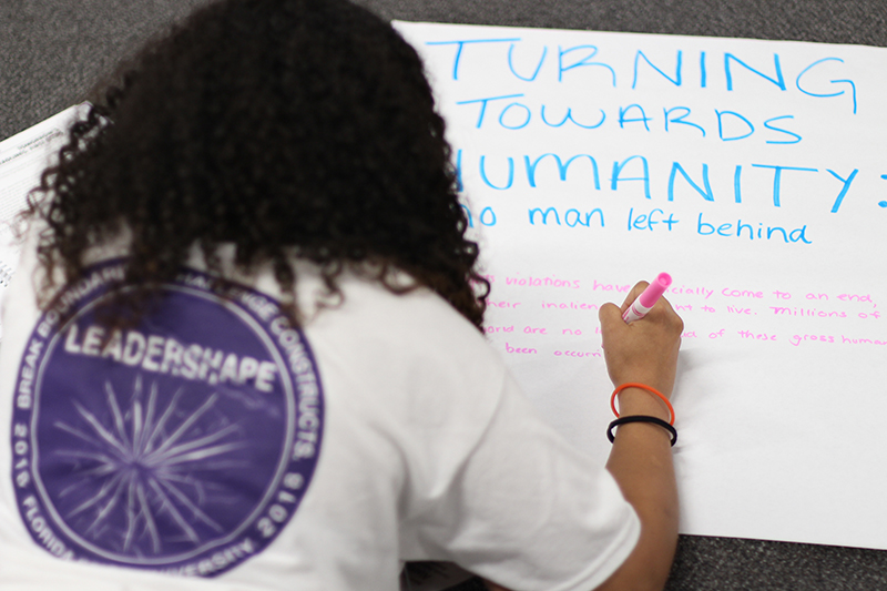 A Leadershape participant writing on a poster paper.