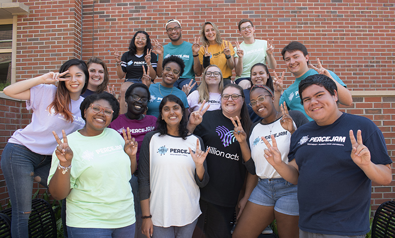 PeaceJam cohort holding up peace signs.
