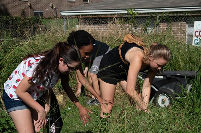 Three EngegeTLH volunteers are knee deep in weeds and overgrowth as they are weeding out the Damayam Community Garden.