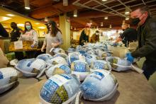 Multiple volunteers organize and prepare turkeys to be packed